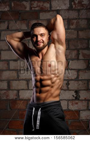 Man athlete posing at a brick wall. Bodybuilder ahead of the competition. Drying. Relief and sculptural body muscles. Healthy lifestyles concept.