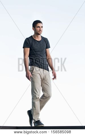 Athletic man in a dark T-shirt on background of sky. Men's beauty. Street fashion.