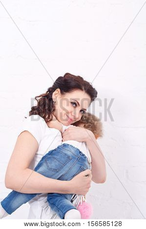 Mother and daughter bear hug. Mother and daughter dressed in jeans and white T-shirts. Family look.