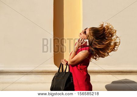 Girl in red dress sunglasses with curly hair and trendy handbag. Girl talking on the phone. Street fashion. Flying hair.