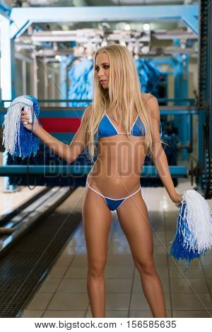 Athletic blonde posing with pom-poms at car wash