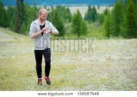 Man uses a smart watch during the run in the mountains. Altay.