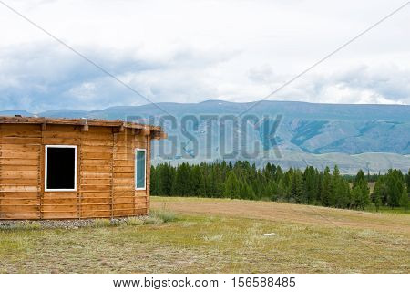 Wooden mountain house on green field. Round house.
