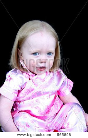 Cute Little Girl Sitting On A Black Background