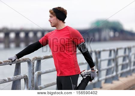 Male runner training in cold winter doing warm-up leg stretching exercise. Young man athlete doing running warm-up before winter run in city outdoor in warm clothing for cold weather.