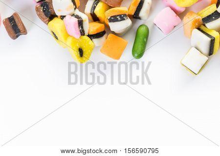 Multicolored mini licorice on a white background.