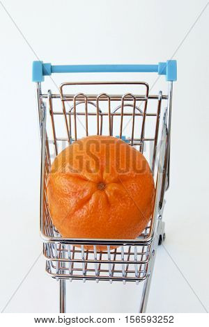 An orange mandarin in a shopping trolley.