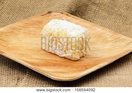 Kuih coconut traditional Malay nyonya sweet desert on palm leaf jute