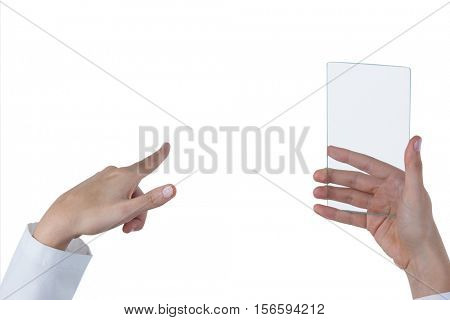 Hands of female doctor using digital screen while holding mobile phone against white background