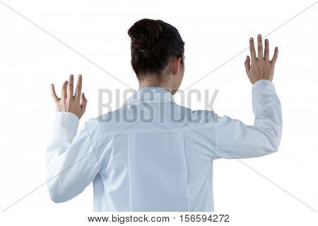 Rear view of female doctor using digital screen against white background