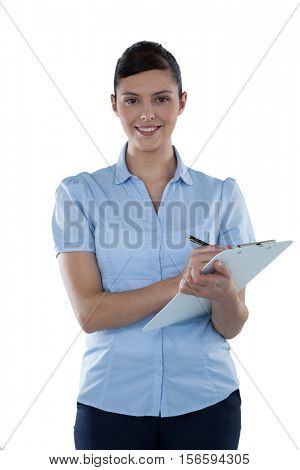 Beautiful businesswoman writing on a clipboard against white background