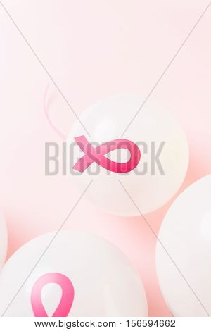 White latex balloons with pink ribbons with a symbol. poster