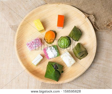 Kuih traditional Malay nyonya sweet desert assorted mix on palm leaf plate jute
