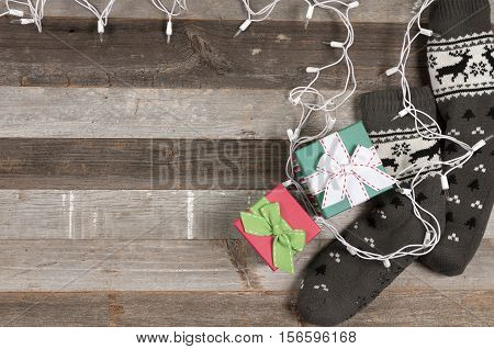 Christmas presents and Christmas ligh. Warm knitted socks on a wooden table.