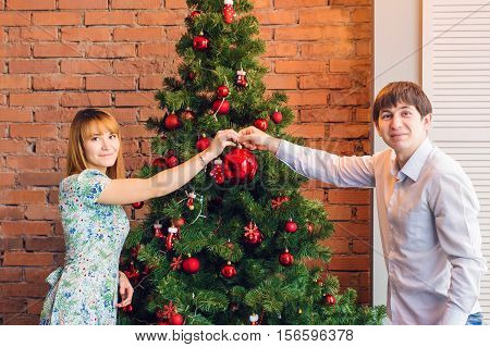 family, x-mas, winter holidays and people concept - happy couple decorating christmas tree at home.