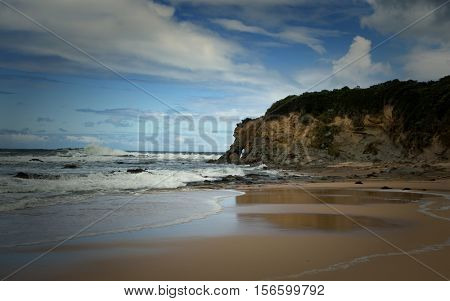 Landscape at  Kilcunda Beach in Australia with the sea of Bass Strait and a blue cloudy sky in background.