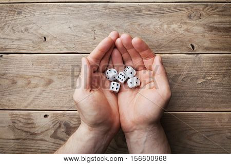 Man holding in hand white dice over the wooden table top view. Gambling devices. Game of chance concept.