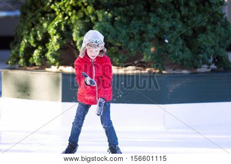 little boy enjoying ice skating at winter at outdoor skating rink decorated for holiday time at snowy weather winter concept