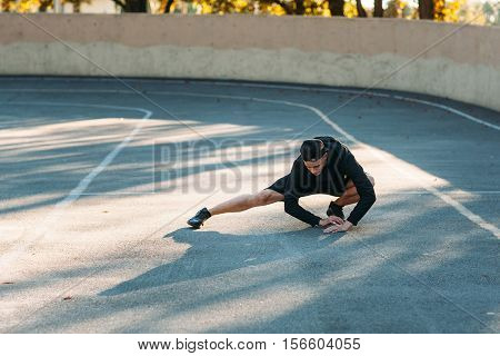 Male marathoner stretching before running. Sprinter training on open-air stadium before competition. Professional sportsman warming-up.