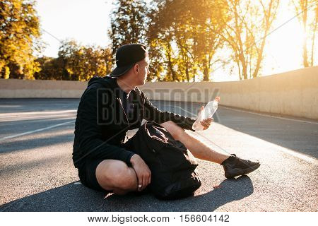 Young sportsman enjoying sunset after training. Sprinter relaxing after hard training with bottle of water. Healthy lifestyle, professional sport concept