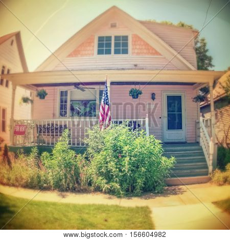Fisheye instagram image of an old house with a porch, blurred shallow focus on door and porch