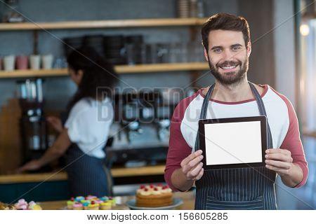 Portrait of smiling waiter showing digital tablet at counter in café