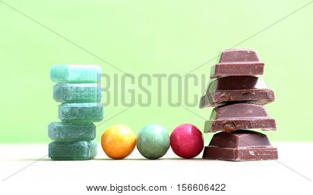 picture of a Green mints candy chocolate pieces and bubble gum on green background.