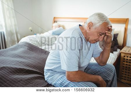 Frustrated senior man sitting on bed in bedroom