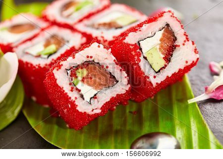 Sushi Roll with Salmon, Avocado and Cream Cheese inside. Tobiko and outside