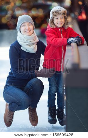 family of two enjoying ice skating at winter at outdoor skating rink decorated for holiday time winter and family concept