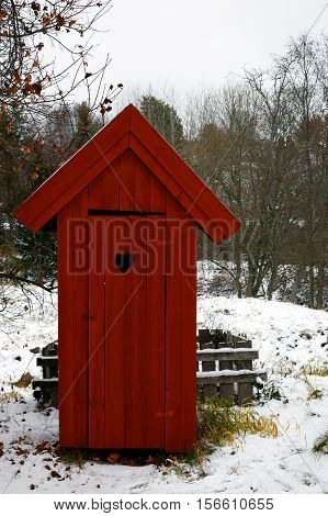Red outhouse toilet in wintertime. Front view.
