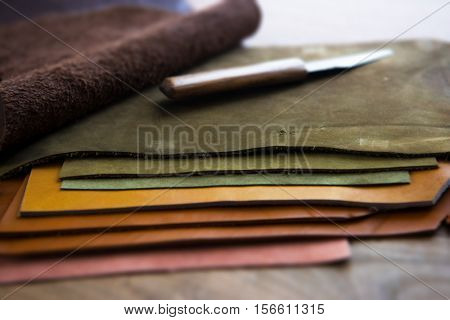 Leather craft or leather working. Pieces of tanned leather on leather craftman's work desk with knife on top. Focus on edge of top piece of hide. Shallow depth of field. Soft focus.