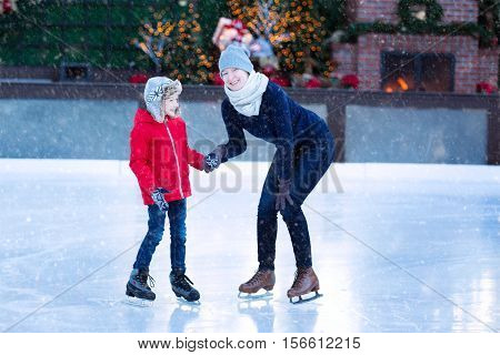 family of two enjoying ice skating at winter at outdoor skating rink decorated for holiday time at snowy weather winter and family concept