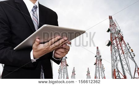 Businessman working on digital tablet, with satellite dish telecom network on telecommunication tower in the morning, telecommunication in business and development