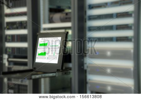 Monitor of monitoring system in data center room with blurred server in rack cabinet