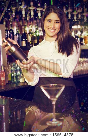 Portrait of bartender mixing cocktail drink in cocktail shaker against flying colours