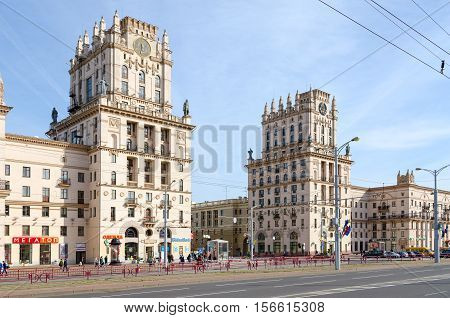 MINSK BELARUS - OCTOBER 1 2016: Unidentified people go on Privokzalnaya square. Architectural complex in style of Stalin's empire which consists of two 11-storey buildings-towers at corners 5-storey buildings known as