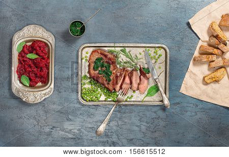 Sliced medium rare grilled steak on the vintage iron tray on stone surface top view