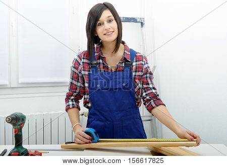pretty young woman builder measuring a plank of wood