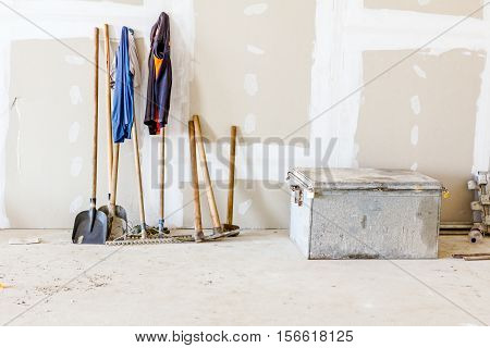 Set of different tools for earthworks are leaning against the wall plasterboard wall.