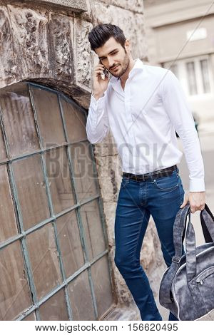 Casual young man walking on the street talking on mobilephone.