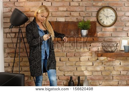 Young woman in retro home standing by brick wall, using mobilephone.