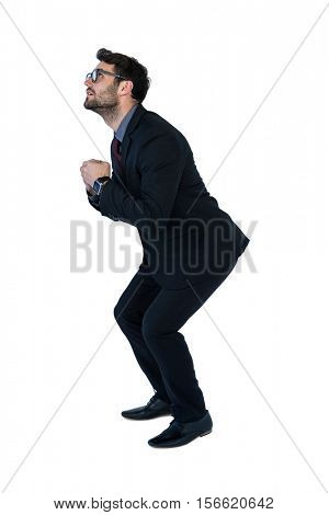 Businessman performing exercise against white background