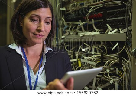 Technician using digital tablet while analyzing server in server room