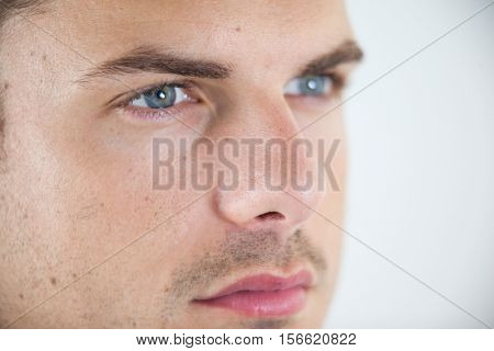 Close-up of man wearing contact lens against white background