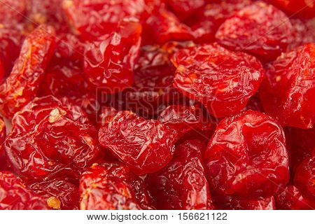 Dried cherries close up background. Heap of glossy red cherry. Top view.