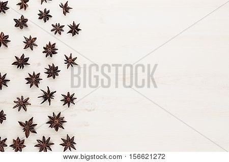 Anise stars spice pattern on white wood background. Christmas decorative frame. Top view.