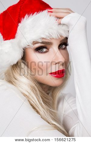 Beautiful Sexy Blonde Female Model Dressed As Santa Claus In A Red Cap With At The White Fur Lovely