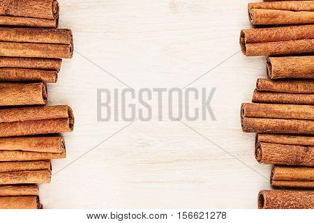 Cinnamon sticks closeup on white wood background. Christmas decorative border of cinnamon sticks spice. Top view.
