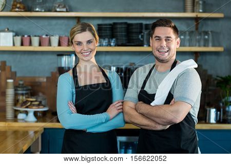 Portrait of smiling waiter and waitress standing with arms crossed in cafe